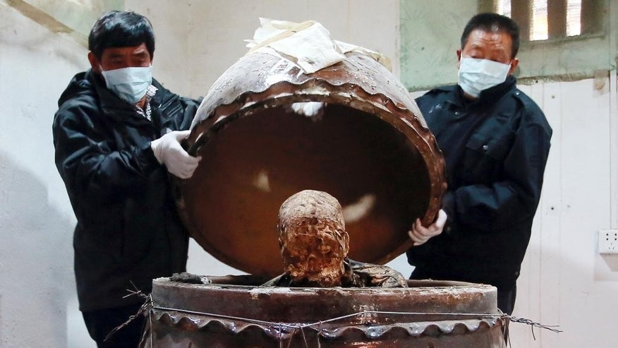 In this photo taken Sunday Jan. 10, 2016, men remove the top of a jar containing the mummified body of revered Buddhist monk Fu Hou in Quanzhou city in southeastern China's Fujian province. The monk, who died in 2012 at the age of 94, was prepared for mummification by his temple to commemorate his devotion to Buddhism. The mummifed remains were then treated and covered in gold leaf, a practice reserved for holy men in some areas with strong Buddhist traditions. (Chinatopix via AP) CHINA OUT