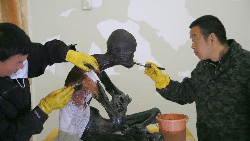 In this photo taken Thursday Jan. 14, 2016, men apply lacquer on the mummified body of revered Buddhist monk Fu Hou in Quanzhou city in southeastern China's Fujian province. The monk, who died in 2012 at the age of 94, was prepared for mummification by his temple to commemorate his devotion to Buddhism. The mummifed remains were then treated and covered in gold leaf, a practice reserved for holy men in some areas with strong Buddhist traditions. (Chinatopix via AP) CHINA OUT