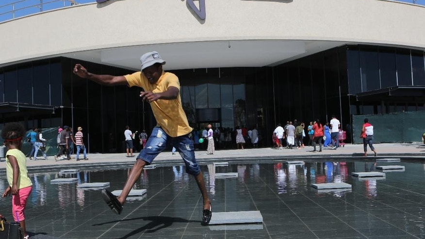 A man jumps from a stepping stone at the entrance to the newly-opened Mall of Africa in Midrand, South Africa, Thursday April 28, 2016.  Thousands of South African shoppers flocked to the opening Thursday of one of Africa's largest malls outside Johannesburg, despite rising unemployment and slowing economic growth, seemingly attracted to the international brand names and opening discounts available. (AP Photo/Denis Farrell)