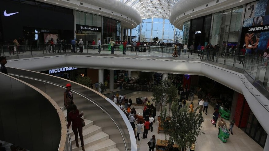 Shoppers make their way along the wide shopping avenues inside the newly-opened Mall of Africa in Midrand, South Africa, Thursday April 28, 2016.  Thousands of South African shoppers flocked to the opening Thursday of one of Africa's largest malls outside Johannesburg, despite rising unemployment and slowing economic growth, seemingly attracted to the international brand names and opening discounts available. (AP Photo/Denis Farrell)