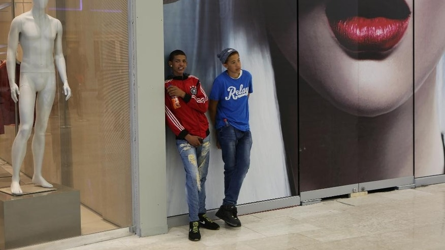Boys hang out in the newly-opened Mall of Africa in Midrand, South Africa, Thursday April 28, 2016.  Thousands of South African shoppers flocked to the opening Thursday of one of Africa's largest malls outside Johannesburg, despite rising unemployment and slowing economic growth, seemingly attracted to the international brand names and opening discounts available.(AP Photo/Denis Farrell)