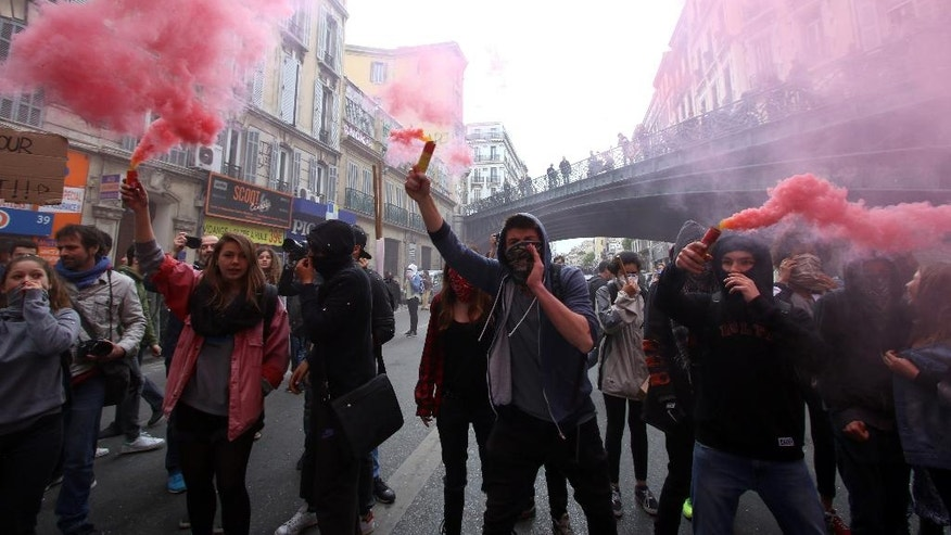 Students burn flares and shout slogans during a demonstration in Marseille, southern France, Thursday, April 28, 2016,  during a nationwide day of protest.  Student organizations and employee unions have joined to call for protests across France to reject a government reform relaxing the 35-hour working week and other labour rules.(AP Photo/Claude Paris)