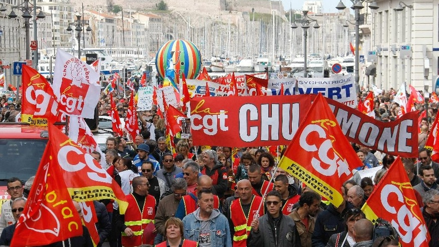 Employees, workers and students demonstrate in the Old-Port, in Marseille, southern France, Thursday, April 28, 2016, during a nationwide day of protest.  Student organizations and employee unions have joined to call for protests across France to reject a government reform relaxing the 35-hour working week and other labour rules. (AP Photo/Claude Paris)