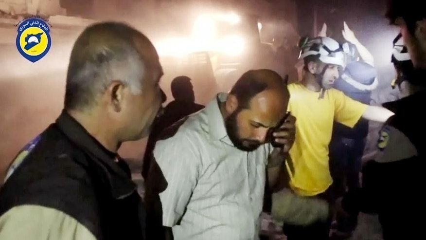 In this image made from video on Wednesday, April 27, 2016 and posted online by the Syrian Civil Defense White Helmets, Civil Defense workers stand in rubble after airstrikes hit a hospital in Aleppo, Syria. A series of airstrikes hit a hospital and adjacent buildings in the rebel-held part of the contested city of Aleppo in Syria on Wednesday night, reportedly killing more than a dozen people. (Syrian Civil Defense White Helmets via AP video)