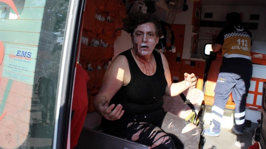 An injured person sits in an ambulance after a suicide bomb attack outside the historical tourist destination at Ulu Cami in Bursa, Turkey, Wednesday, April 27, 2016.  The office of the governor of Bursa said in a statement carried by the state-owned Anadolu Agency that a woman believed to be a suicide bomber blew herself up. (IHA agency via AP ) TURKEY OUT