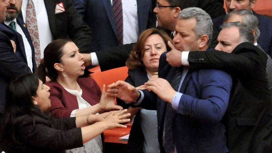Turkish lawmakers argue and push each other on the assembly floor in Ankara, Turkey, late Wednesday, April 27, 2016.  Turkish lawmakers on Thursday argued and pushed each other as they debated a contentious ruling-party proposals.(AP Photo)