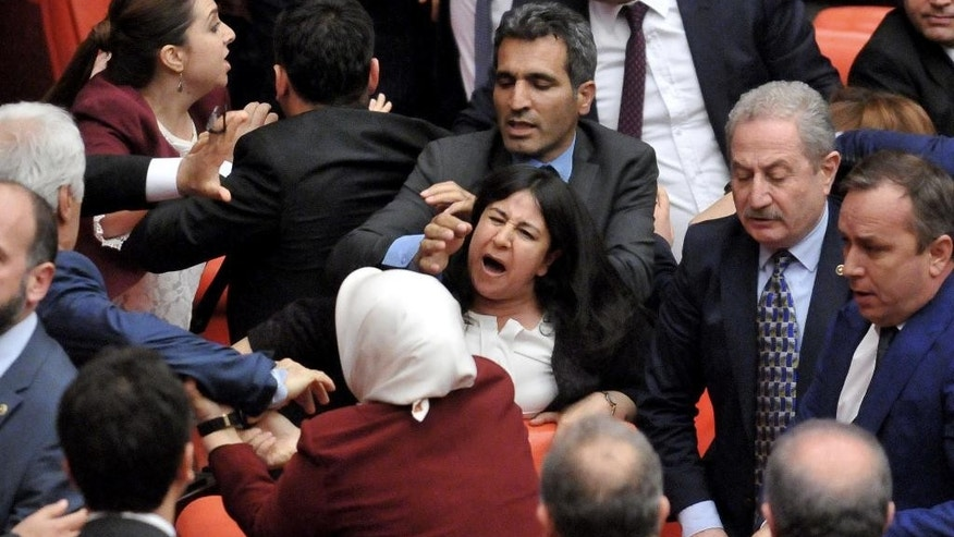 Turkish lawmakers argue and push each other on the assembly floor in Ankara, Turkey, late Wednesday, April 27, 2016.  Turkish lawmakers on Thursday argued and pushed each other as they debated contentious ruling-party proposals.(AP Photo)