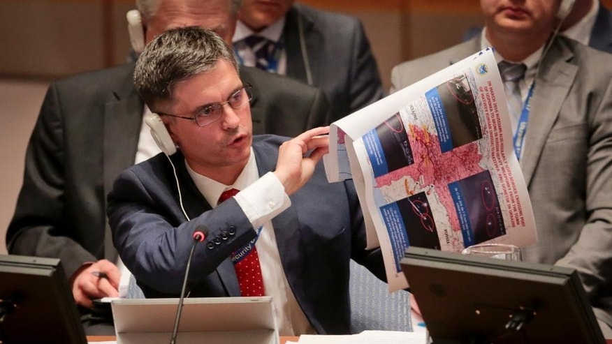 Ukraine's Deputy Foreign Minister Vadym Prystiako display graphics during a Security Council meeting on the conflict in Ukraine, Thursday, April 28, 2016 at U.N. headquarters. Fighting between Russia-backed separatists and Ukrainian government forces has claimed thousands of lives over the past two years. (AP Photo/Bebeto Matthews)