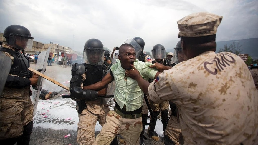 A supporter of the PHTK presidential candidate Jovenel Moise, is arrested by national police officers in front of the parliament building during a protest to demand the government restart the electoral process for a presidential runoff that has been postponed three times, in Port-au-Prince, Haiti, Thursday, April 28, 2016. The U.S. State Department's special coordinator for Haiti arrived Thursday seeking to help resolve a political standoff that has left elections in the Caribbean nation in limbo. (AP Photo/Dieu Nalio Chery)