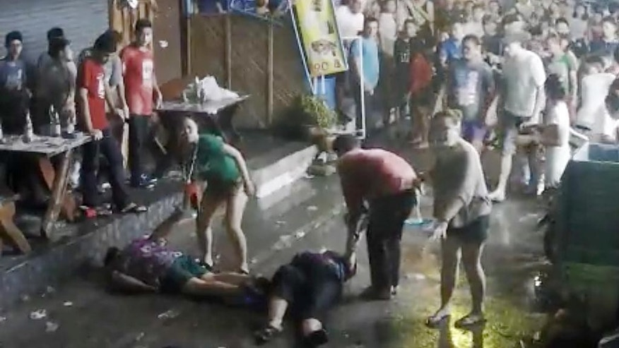 In this April 13, 2016 image taken from video released by the Hua Hin Municipality an elderly British couple and their son are on the ground after they were savagely attacked during a family vacation in Hua, Hin, Thailand. A video of the attack, which was captured by overhead security cameras and posted this week on social media, has stirred shock and outrage over its brutality and the ages of the elder victims, a 65-year-old woman and 68-year-old man from Scotland. The attack marks the latest act of violence against tourists in the Southeast Asian country. (Hua Hin Municipality via AP)