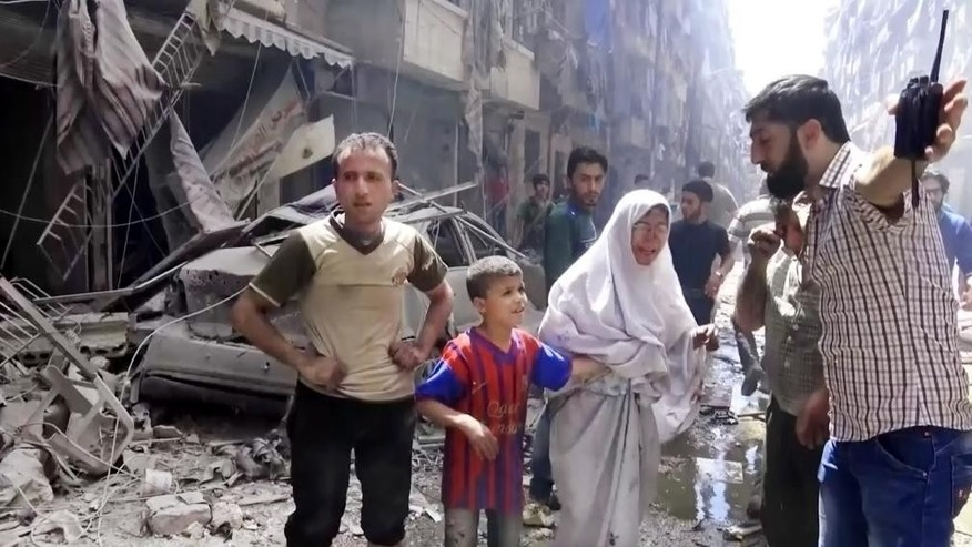 In this image made from video and posted online from Validated UGC, a man leads a woman in tears and child out of the scene after airstrikes hit Aleppo, Syria, Thursday, April 28, 2016. A Syrian monitoring group and a first-responders team say new airstrikes on the rebel-held part of the contested city of Aleppo have killed over a dozen people and brought down at least one residential building. The new violence on Thursday brings the death toll in the past 24-hours in the deeply divided city to at least 61 killed. (Validated UGC via AP video)
