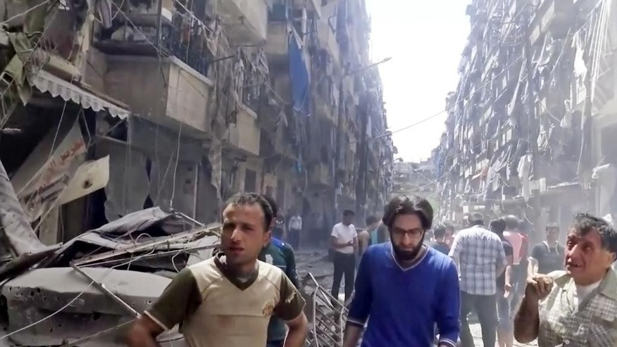 In this image made from video and posted online from Validated UGC, men look at damaged buildings after airstrikes hit Aleppo, Syria, Thursday, April 28, 2016. A Syrian monitoring group and a first-responders team say new airstrikes on the rebel-held part of the contested city of Aleppo have killed over a dozen people and brought down at least one residential building. The new violence on Thursday brings the death toll in the past 24-hours in the deeply divided city to at least 61 killed. (Validated UGC via AP video)