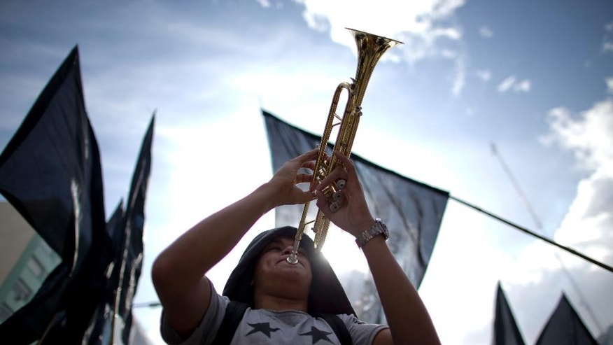 A worker plays a trumpet during a protest against skyrocketing consumer prices and job cuts in Buenos Aires, Argentina, Friday, April 29, 2016. Thousands of state employees have been fired since Argentina's President Mauricio Macri came to power in December with promises to cut spending. The protest was staged ahead of Sunday's May 1 Labor Day. (AP Photo/Natacha Pisarenko)