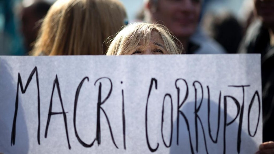 "A woman holds a sign that reads in Spanish: ""Macri corrupt,"" referring to Argentina's President Mauricio Macri, during a protest against skyrocketing consumer prices and job cuts in Buenos Aires, Argentina, Friday, April 29, 2016. Thousands of state employees have been fired since Macri came to power in December with promises to cut spending. The protest is staged ahead of Sunday's May 1 Labor Day. (AP Photo/Natacha Pisarenko)"