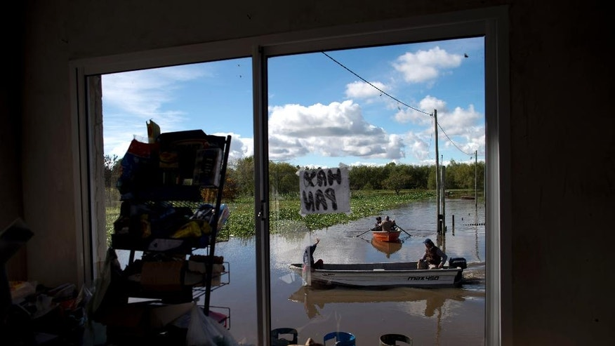 People row boats on a flooded street of Villa Paranacito, Entre Rios, Argentina, Thursday, April 28, 2016. The Argentine Red Cross estimates that around 30,000 people have been affected after rains swelled rivers, swamping fields and towns nationwide. (AP Photo/Natacha Pisarenko)