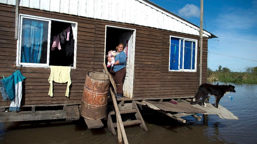 Margaret Chozza stands outside her house on the flooded town of Villa Paranacito, Entre Rios, Argentina, Thursday, April 28, 2016. The Argentine Red Cross estimates that around 30,000 people have been affected after rains swelled rivers, swamping fields and towns nationwide. (AP Photo/Natacha Pisarenko)