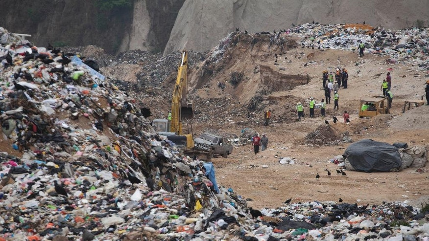Rescue workers search the city dump for survivors one day after trash collapsed on workers in Guatemala City, Thursday, April 28, 2016. Rescue workers are picking through garbage looking for bodies or possible survivors after the massive slope of trash collapsed, killing at least four people.  Authorities say about 1,000 people worked in that area of the dump. (AP Photo/Moises Castillo)