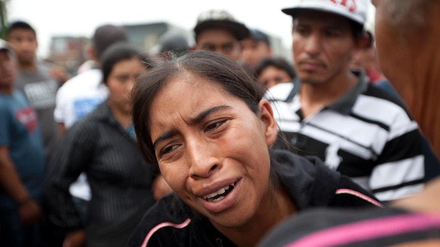 The relative of a missing garbage-picker cries as she waits for information at the entrance of the city garbage dump in Guatemala City, Thursday, April 28, 2016. Rescue workers are picking through garbage looking for bodies or possible survivors a day after the massive slope of trash collapsed, killing at least four people.  Authorities say about 1,000 people worked in that area of the dump. (AP Photo/Moises Castillo)