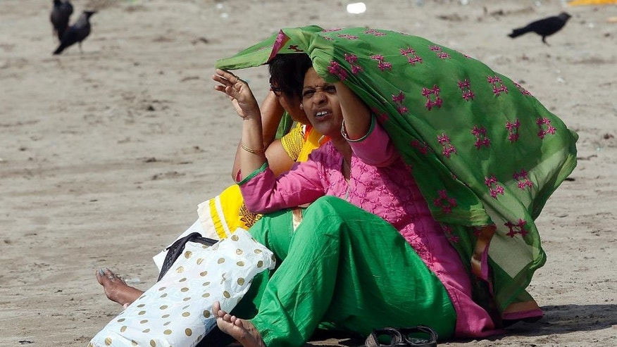 Indian women cover themselves with a cloth to protect from direct Sun in Mumbai, India, Friday, April 29, 2016. With sizzling temperatures claiming more than 300 lives this month in India, officials said Friday they were banning daytime cooking in some parts of the drought-stricken country in a bid to prevent accidental fires that have killed nearly 80 more people. (AP Photo/ Rajanish Kakade )