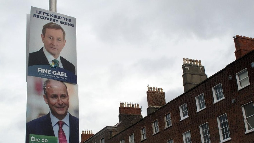 FILE - This  is a  Feb. 5, 2016 file photo, of  rival election posters for Fine Gael leader Enda Kenny and Fianna Fail leader Micheal Martin as they adorn a lamp post in Dublin. Ireland's two key parties said Friday night, April 29, 2016, they have struck a deal to create a new, fragile government following an inconclusive election and two months of political deadlock. (AP Photo/Shawn Pogatchnik, File)