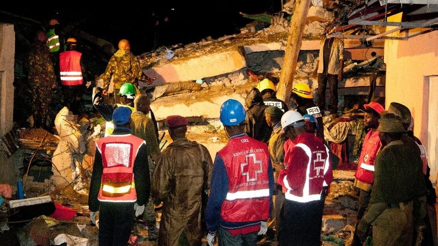 Kenya Red Cross personnel work at the site of a building collapse in Nairobi, Kenya, Saturday, April 30, 2016. A six-story residential building in a low income area of the Kenyan capital collapsed Friday under heavy rain and flooding, trapping an unknown number of people in the rubble, Kenyan officials said.(AP Photo/Sayyid Abdul Azim)