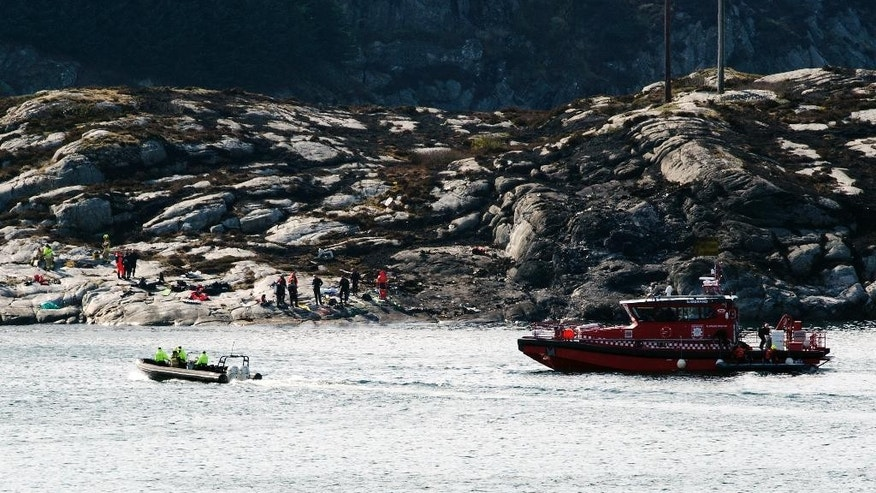 A search and rescue vessel patrols off the island of Turoey, near Bergen, Norway, as emergency workers attend on the shoreline after a helicopter crashed believed to have 13 people aboard, Friday April 29, 2016.  A helicopter carrying around 13 people from an offshore oil field crashed Friday near the western Norwegian city of Bergen, police said. Many are feared dead.  (Marit Hommedal / NTB scanpix via AP) NORWAY OUT