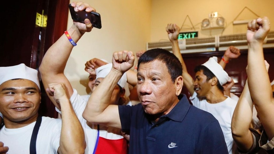 Philippines presidential candidate Rodrigo Duterte, center, clenches his fist as he is cheered by kitchen staff of a Chinese restaurant following his meeting with some politicians who shifted political support to his camp Friday, April 29, 2016 in Manila, Philippines. Duterte is facing another controversy after allegedly failing to declare his P211 million Pesos (U.S. $4.5 million) 2014 bank deposits as required by law. (AP Photo/Bullit Marquez)