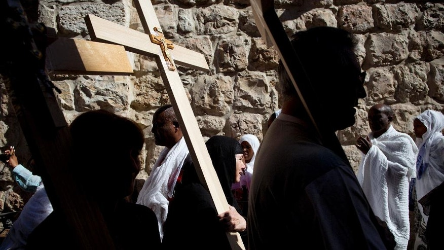 Orthodox Christians hold crosses as they wait to walk along the Via Dolorosa towards the Church of the Holy Sepulchre, traditionally believed by many to be the site of the crucifixion of Jesus Christ, during the Good Friday procession in Jerusalem's Old City, Friday, April 29, 2016. (AP Photo/Oded Balilty)