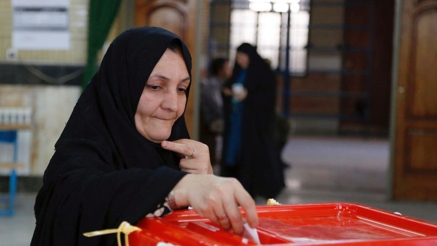 An Iranian woman casts her ballot for the parliamentary runoff elections in a polling station at the city of Qods about 12 miles (20 kilometers) west of the capital Tehran, Iran, Friday, April 29, 2016. Iranians voted Friday in the country's parliamentary runoff elections, a key polling that is expected to decide exactly how much power moderate forces backing President Hassan Rouhani will have in the next legislature. The balloting is for the remaining 68 positions in the 290-seat chamber that were not decided in February's general election, in which Rouhani's allies won an initial majority. (AP Photo)
