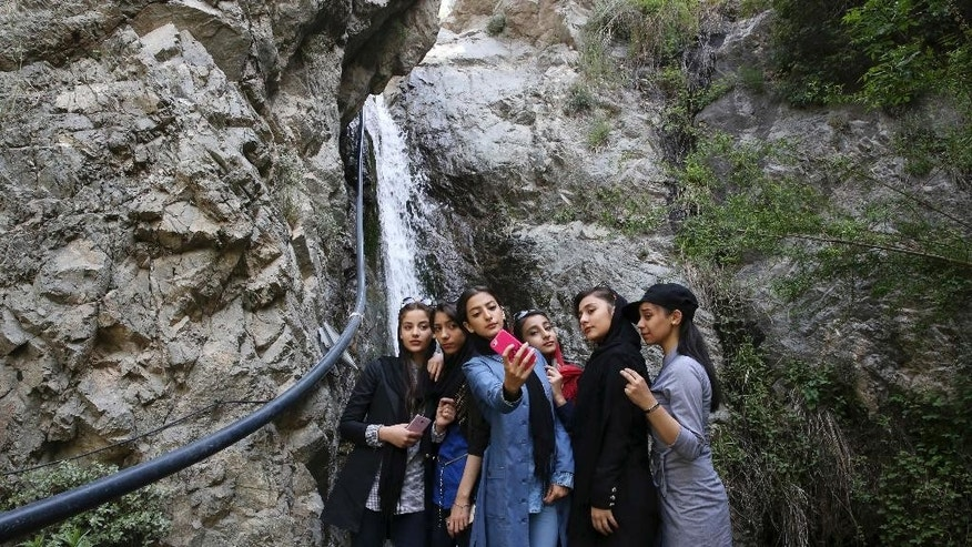 Iranian teenagers take selfie while enjoying their time at the Tochal mountainous area northern Tehran, Iran, Friday, April 29, 2016. While Tehran citizens are enjoying their time on a spring weekend many people in 55 constituencies, including cities and towns across the nation are voting to decide 68 seats of the 290-member parliament. (AP Photo/Vahid Salemi)