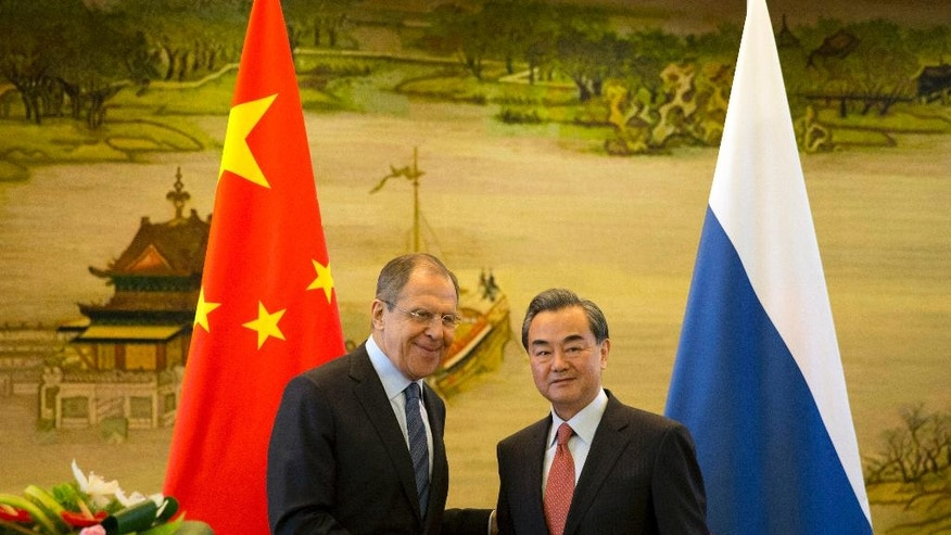 Russian Foreign Minister, Sergey Lavrov, left, and Chinese Foreign Minister Wang Yi shakes hands after a joint press conference held at the Chinese Foreign Ministry in Beijing, China, Friday, April 29, 2016. (AP Photo/Ng Han Guan)