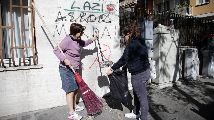 Volunteers clean a sidewalk as part of the Retake Rome gathering in Rome, Sunday, April 10, 2016. Tired of waiting years for the city to replace diseased trees and do other work, Romans are starting to take back their city. (AP Photo/Gregorio Borgia)