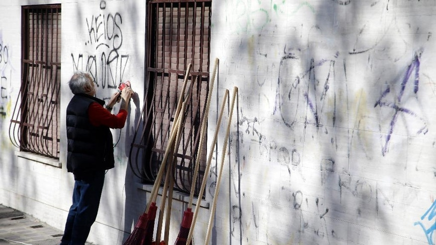 A man cleans graffiti from a wall as past of the Retake Rome gathering in Rome, Sunday, April 10, 2016. Tired of waiting years for the city to replace diseased trees and do other work, Romans are starting to take back their city. (AP Photo/Gregorio Borgia)