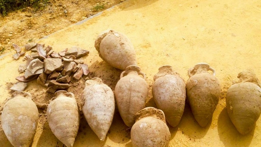 This photo made available by the City Council of Tomares on Friday, April 29, 2016, shows some of the 19 amphoras containing thousands of unused bronze and silver-coated coins dating from the end of the 4th century. Workers laying pipes in a southern Spanish park have unearthed a 600-kilogram (1,300-pound) trove of Roman coins in what culture officials say is a unique historic discovery. (City Council of Tomares via AP)