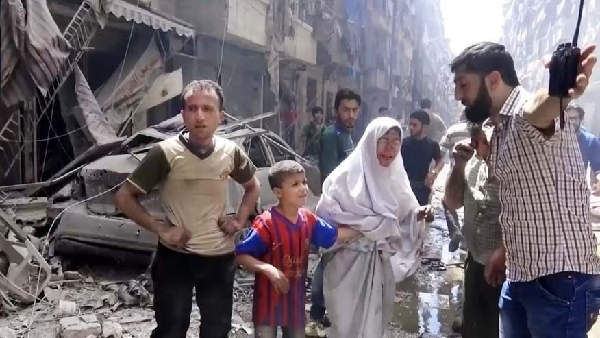 April 28, 2016: In this image made from video and posted online from Validated UGC, a man leads a woman in tears and child out of the scene after airstrikes hit Aleppo, Syria.