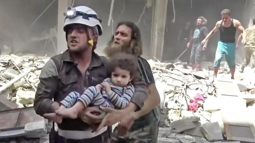 In this image made from video and posted online from Validated UGC, a Civil Defense worker carries a child after airstrikes hit Aleppo, Syria, Thursday, April 28, 2016. A Syrian monitoring group and a first-responders team say new airstrikes on the rebel-held part of the contested city of Aleppo have killed over a dozen people and brought down at least one residential building. The new violence on Thursday brings the death toll in the past 24-hours in the deeply divided city to at least 61 killed. (Validated UGC via AP video)