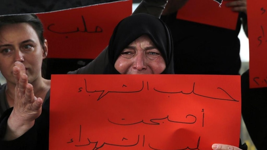 "A Syrian woman weeps as she holds an Arabic placard that reads ""Aleppo has become the Aleppo of martyrs,"" during a protest in downtown Beirut, Lebanon, Saturday, April 30, 2016, against Syrian President Bashar Assad's military operations against areas held by insurgents around the country, mostly in the northern city of Aleppo that has been the main point of violence. (AP Photo/Bilal Hussein)"