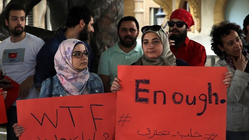"Protesters hold placards during a protest in downtown Beirut, Lebanon, Saturday, April 30, 2016, against Syrian President Bashar Assad's military operations against areas held by insurgents around the country, mostly in the northern city of Aleppo that has been the main point of violence. The Arabic placard read: ""Enough, Aleppo is burning."" (AP Photo/Bilal Hussein)"