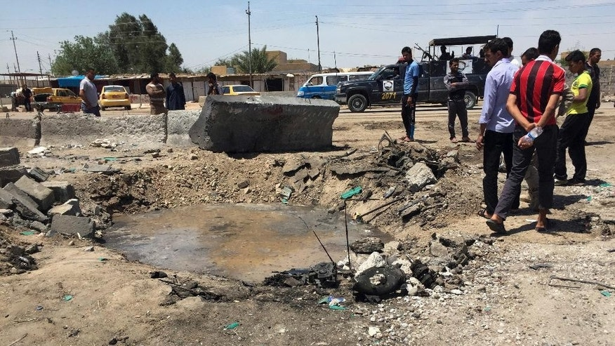Civilians inspect a crater caused by a car bombing at an open-air market selling fruit, vegetables and meat in Baghdad's southeast suburb of Nahrawan, Iraq, Saturday, April 30, 2016. The Islamic State group claimed responsibility for a bombing Saturday east of Baghdad, according to a statement posted on an IS-affiliated website. The attack and wounded scores of civilians according to Iraqi police and hospital officials. The IS statement described the attack as a three-ton truck bombing. (AP Photo/Ali Abdul Hassan)