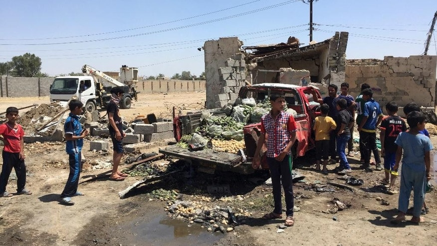 Civilians inspect the scene of car bombing at an open-air market selling fruit, vegetables and meat in Baghdad's southeast suburb of Nahrawan, Iraq, Saturday, April 30, 2016. The Islamic State group claimed responsibility for a bombing Saturday east of Baghdad, according to a statement posted on an IS-affiliated website. The attack and wounded scores of civilians according to Iraqi police and hospital officials. The IS statement described the attack as a three-ton truck bombing. (AP Photo/Ali Abdul Hassan)