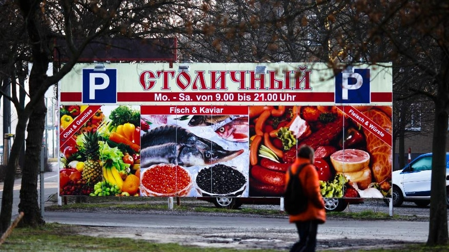 In this photo taken Wednesday, March 9, 2016 pedestrian passes an advertisement poster of a supermarket offering Russian food and products in Berlin, Germany. Germany is seeking to quickly integrate migrants into nation's society and labor force after arrival of over 1 million last year, with Syrians making up the largest group. (AP Photo/Markus Schreiber)