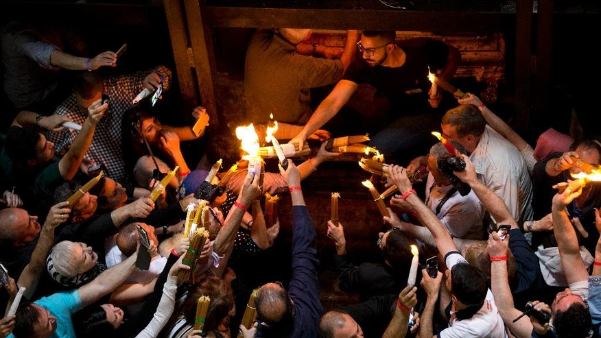 Christian Orthodox pilgrims hold candles during the Holy Fire ceremony in the church of the Holy Sepulchre, traditionally believed to be the burial site of Jesus Christ, Saturday, April 30, 2016 in Jerusalem. Thousands of Christians have gathered in Jerusalem for the ancient fire ceremony that celebrates Jesus' resurrection. (AP Photo/Dusan Vranic)