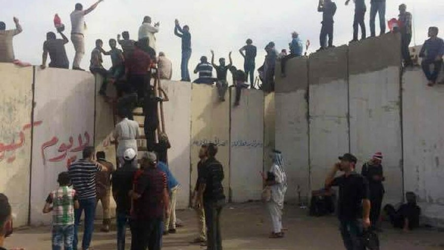 Supporters of Shiite cleric Muqtada al-Sadr climb onto the blast walls outside Baghdad's Green Zone,  Saturday, April 30, 2016. Dozens of protesters climbed over the blast walls  and could be seen storming the Parliament building, carrying Iraqi flags and chanting against the government. (AP Photo/Khalid Mohammed)