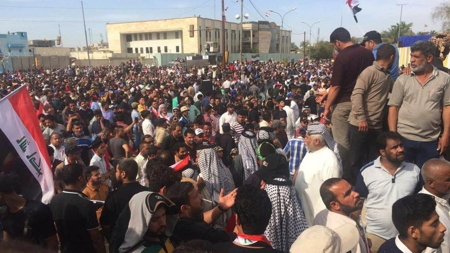 Supporters of Shiite cleric Muqtada al-Sadr protest outside parliament in Baghdad's Green Zone,  Saturday, April 30, 2016. Dozens of protesters climbed over the blast walls  and could be seen storming the Parliament building, carrying Iraqi flags and chanting against the government. (AP Photo/Khalid Mohammed)