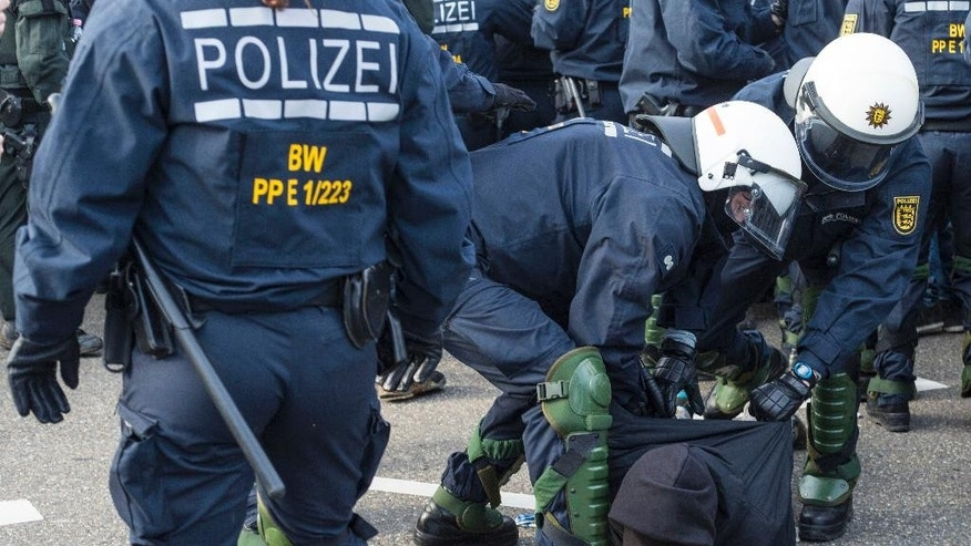 Police detain a leftist demonstrator on the occasion of a party convention of the Alternative for Germany, or AfD, in Stuttgart, Germany Saturday, April 30, 2016. (Christoph Schmidt/dpa via AP)