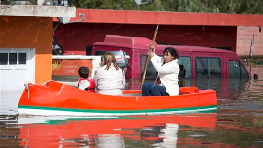 A woman rows a boat on a flooded street of Villa Paranacito, Entre Rios, Argentina, Thursday, April 28, 2016. The Argentine Red Cross estimates that around 30,000 people have been affected after rains swelled rivers, swamping fields and towns nationwide. (AP Photo/Natacha Pisarenko)