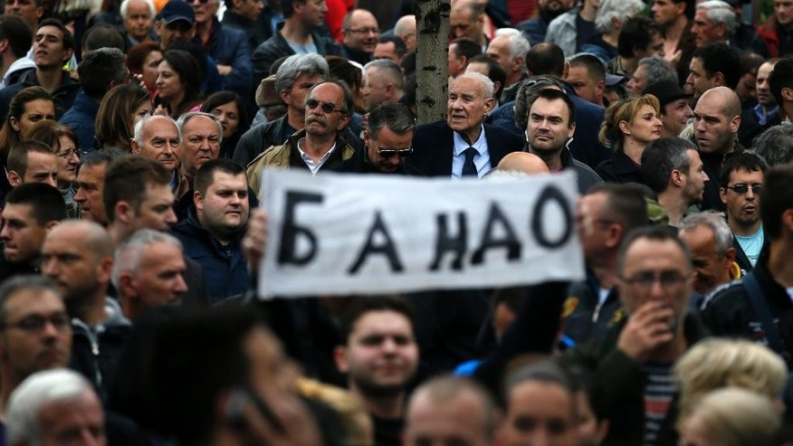 "A man holds a banner reading ""Gang"" in Serbian cyrillic during an opposition protest in Belgrade, Serbia, Saturday, April 30, 2016. Thousands of opposition supporters have protested in front of the Serbian state electoral commission what their leaders are saying is widespread vote rigging by the ruling populists. (AP Photo/Darko Vojinovic)"