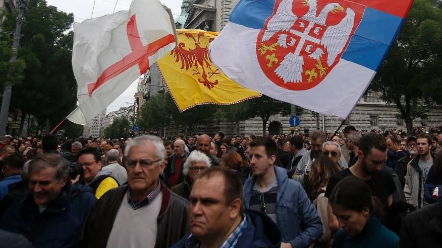 Opposition supporters wave flags during an opposition protest in Belgrade, Serbia, Saturday, April 30, 2016. Thousands of opposition supporters have protested in front of the Serbian state electoral commission what their leaders are saying is widespread vote rigging by the ruling populists. (AP Photo/Darko Vojinovic)