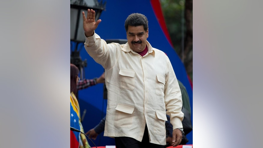 File-This April 19, 2016, file photo shows Venezuela's President Nicolas Maduro greeting supporters upon his arrival to Bolivar Square to celebrate the 206th anniversary of the call for independence from Spain, in Caracas, Venezuela.  The president is ordering a 30 percent increase in the minimum wage, the latest move by the socialist government to grapple with high inflation and economic stagnation. The boost announced Saturday, April 30, 2016, by Maduro comes after a 25 percent increase on March 1. (AP Photo/Fernando Llano, File)