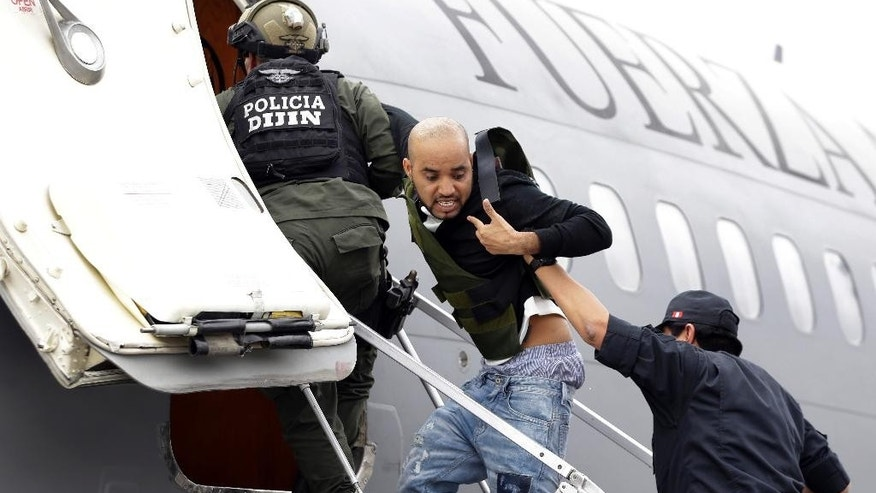 Alleged Peruvian drug trafficker Gerson Galvez shouts at the press as he is escorted by police officers into a Peruvian Air Force plane, in Bogota, Colombia, Sunday, May 1, 2016. Galvez who is one of Peru's most wanted criminals was captured by the Colombian police in Medellin on Saturday and was handed over to the Peruvian authorities. (AP Photo/Fernando Vergara)